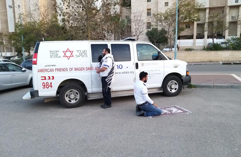 Two paramedics, a Jew wearing a prayer shawl and a Muslim using a prayer mat, pray beside each other near a Magen David Adom (MDA) ambulance in Beersheba, southern Israel, March 24, 2020 (photo credit: MOHAMD ALNBARE/MDA SPOKESPERSON)