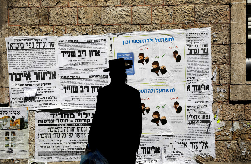 A Jewish ultra-Orthodox man looks onto a local billboard with instructions related to the coronavirus at a street in a Jewish Orthodox neighborhood in Jerusalem, March 27, 2020 (photo credit: REUTERS/Ronen Zvulun)