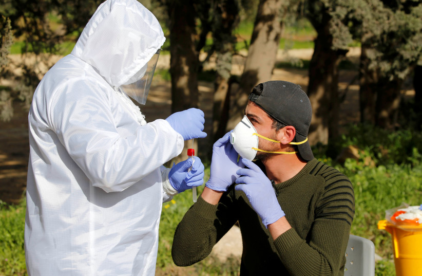A member of medical staff swaps a Palestinian worker for coronavirus disease (COVID-19) testing, upon his return from Israel, outside the Israeli-controlled Tarqumiya checkpoint near Hebron in the Israeli-occupied West Bank March 26, 2020 (photo credit: MUSSA QAWASMA / REUTERS)