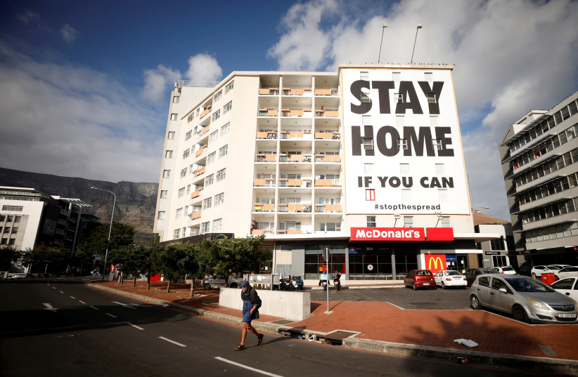A man walks past a poster covering the side of a building ahead of a 21 day lockdown aimed at limiting the spread of coronavirus disease (COVID-19), in Cape Town, South Africa, March 26, 2020. (photo credit: MIKE HUTCHINGS / REUTERS)