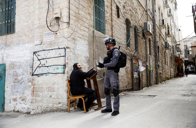 Un homme juif ultra-orthodoxe parle à un policier israélien après que la police l'ait sorti d'une synagogue avant de la fermer, car ils imposent des restrictions de verrouillage partiel contre la maladie à coronavirus (COVID-19) dans le quartier Mea Shearim de Jérusalem le 30 mars 2020. ( crédit photo: RONEN ZVULUN / REUTERS)