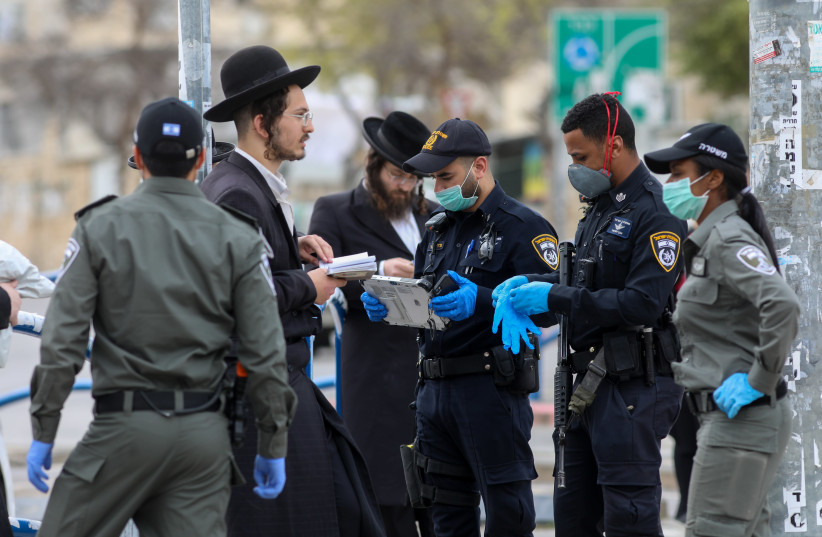 Police officers close synagogues and disperse public gatherings in an ultra orthodox Jewish neighborhood in Beit Shemesh, following the government's decisions, in an effort to contain the spread of the coronavirus on March 31, 2020 (photo credit: YAAKOV LEDERMAN)
