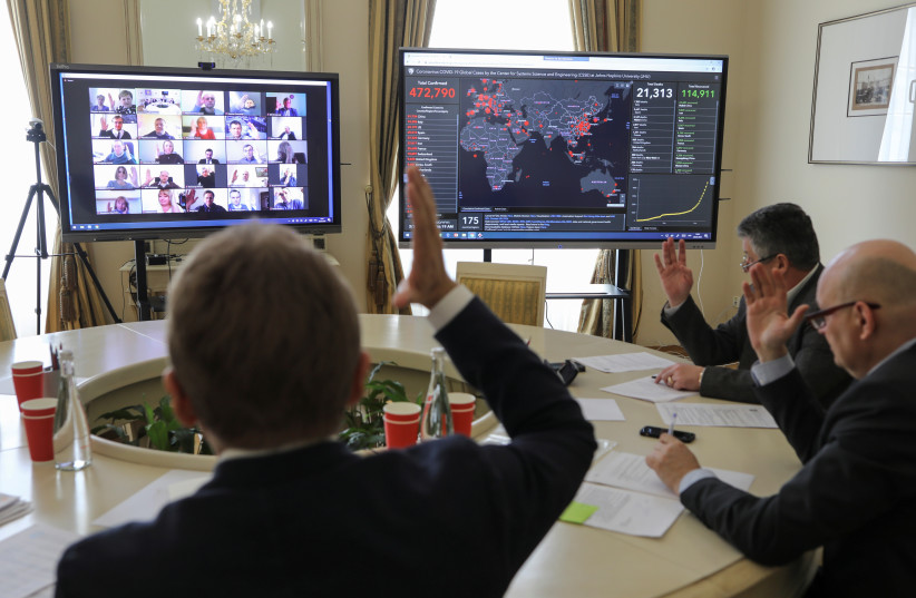 Members of the city commission to prevent the spread of coronavirus disease (COVID-19) vote during a meeting via Zoom video link in Lviv, Ukraine March 26, 2020. (photo credit: REUTERS/ROMAN BALUK)