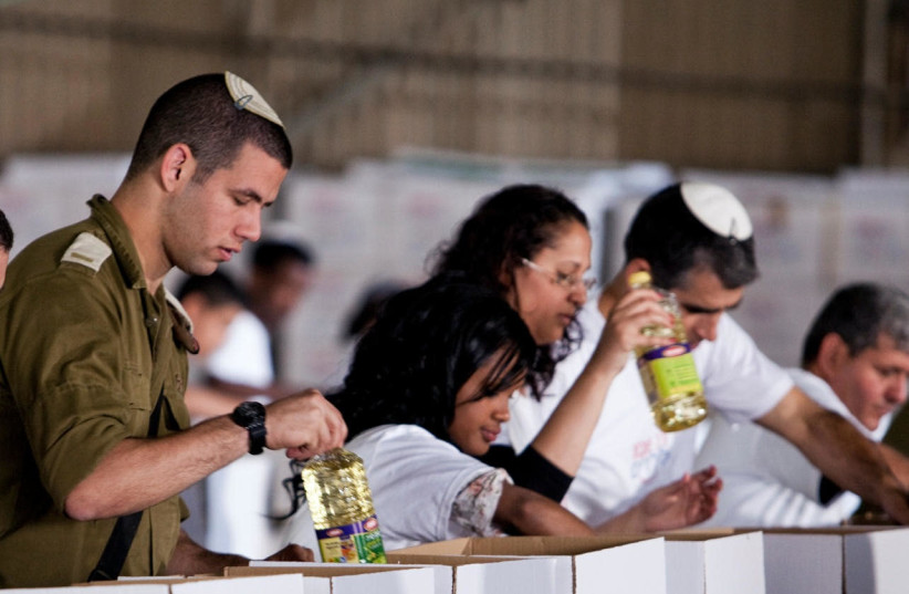 Israelis placing food in charity boxes  (photo credit: Courtesy)