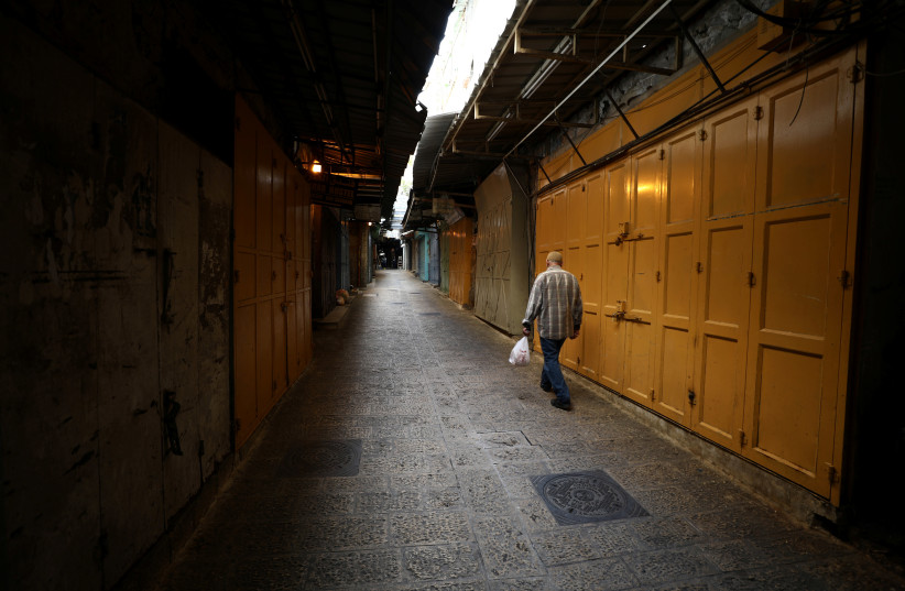 A man walks in an alley inside Jerusalem's Old CIty as shops are closed amid coronavirus restrictions in the walled Old City March 27, 2020 (photo credit: REUTERS/AMMAR AWAD)