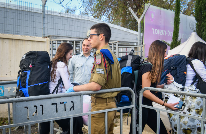 Young Israelis arrive to the Israeli army recruitment center at Tel Hashomer, outside of Tel Aviv on March 17, 2020. (photo credit: FLASH90)