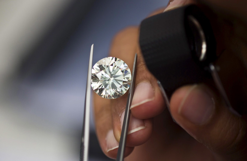 A trader inspects a diamond during a show at Israel's Diamond Exchange near Tel Aviv, Israel (photo credit: REUTERS)