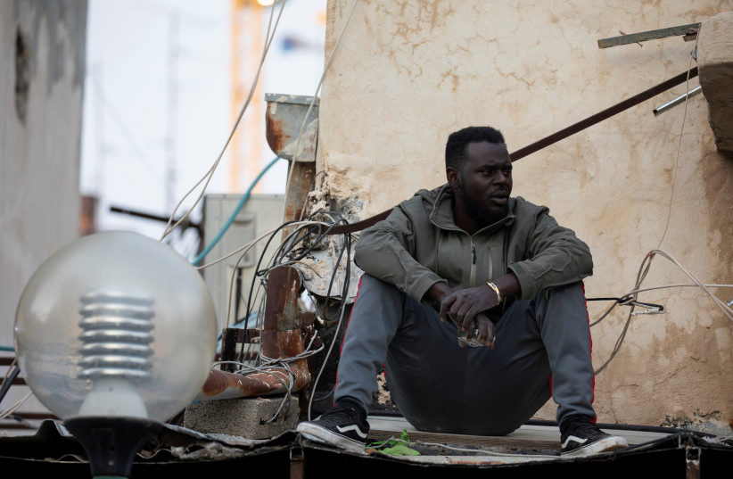 An African migrant sits near the Old Central Bus Station in south Tel Aviv, Israel February 3, 2020 (photo credit: REUTERS/AMIR COHEN)