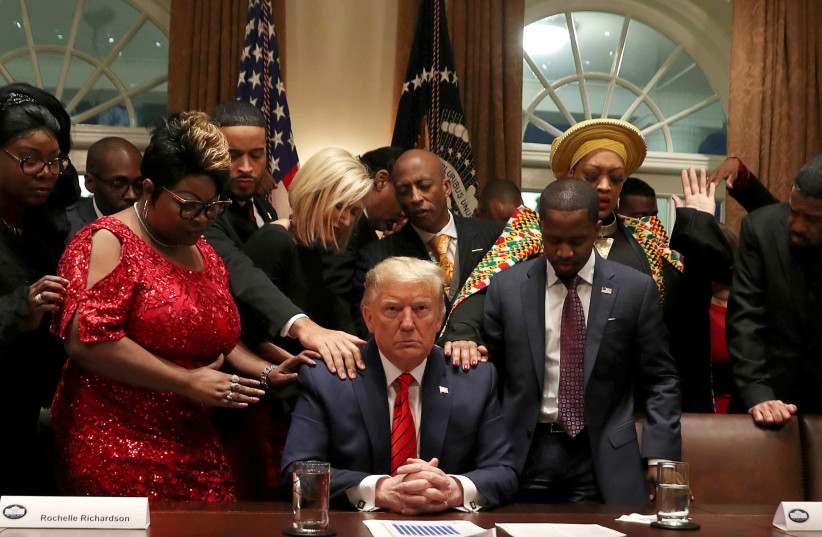 African-American supporters, including Terrence Williams, Angela Stanton and Diamond and Silk, pray with U.S. President Donald Trump in the Cabinet Room of the White House in Washington, US. (photo credit: REUTERS)