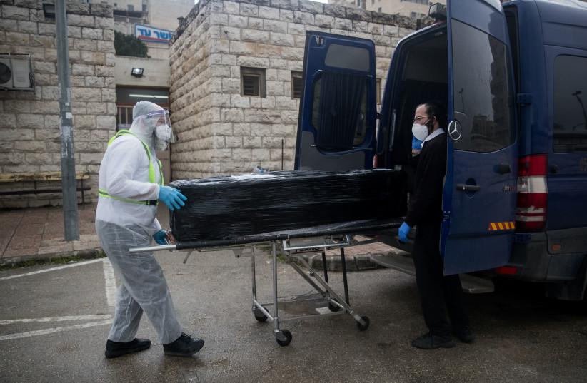 Des travailleurs de Chevra Kadisha portant des vêtements de protection, portent le corps d'un patient décédé des complications d'une infection par le coronavirus (COVID-19), au salon funéraire Shamgar à Jérusalem le 1er avril 2020 (crédit photo: YONATAN SINDEL / FLASH90)