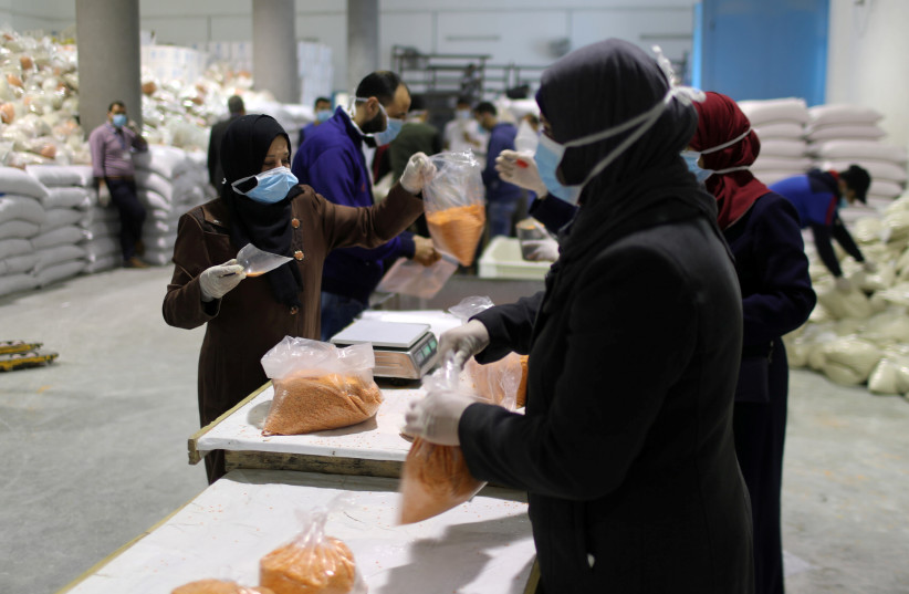 Workers pack food supplies to be distributed and delivered by the United Nations Relief and Works Agency (UNRWA) to the homes of Palestinian refugees as a precaution against the spread of coronavirus disease (COVID-19), in the northern Gaza Strip March 31, 2020 (photo credit: REUTERS/MOHAMMED SALEM)