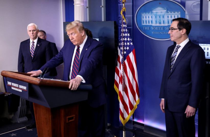 US President Donald Trump addresses the daily coronavirus response briefing as Vice President Mike Pence and Treasury Secretary Steven Mnuchin listen at the White House in Washington, US, April 2, 2020 (photo credit: REUTERS)