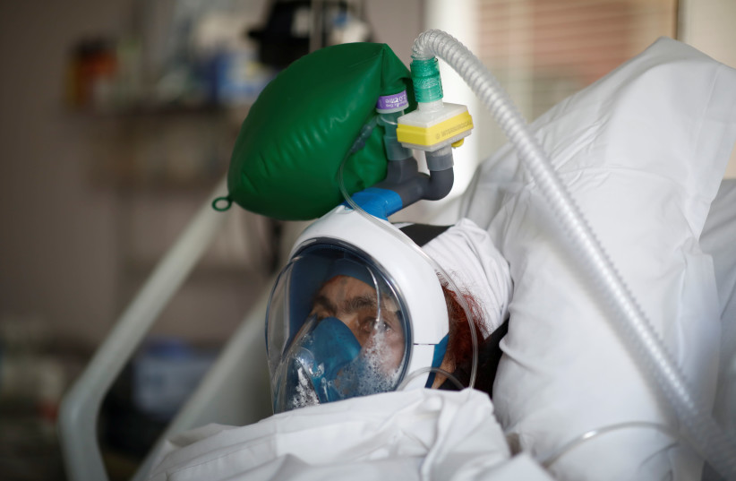A patient suffering from coronavirus disease (COVID-19) wears a full-face Easybreath snorkelling mask given by sport chain Decathlon and turned into a ventilator for coronavirus treatment (photo credit: REUTERS/BENOIT TESSIER)