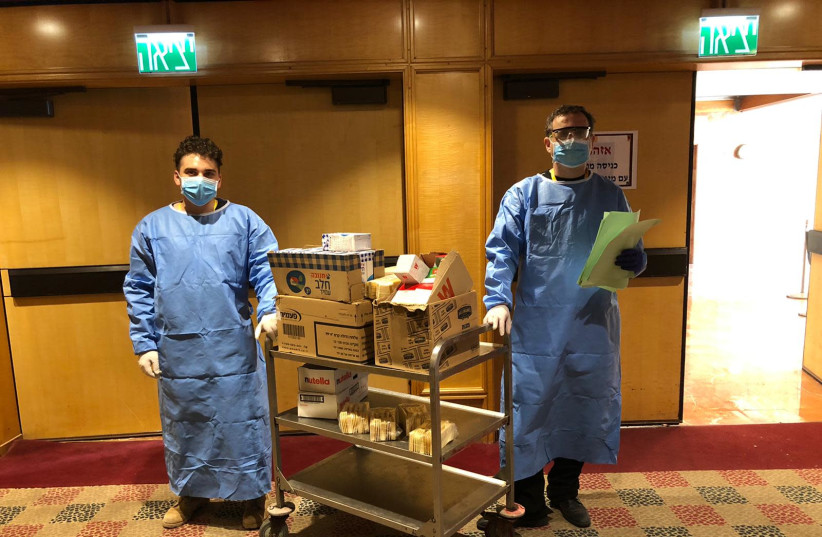Members of the hotel staff wear protective gear while serving food at the Dan Panorama Hotel in Tel Aviv. (photo credit: AMIT KATZAV)