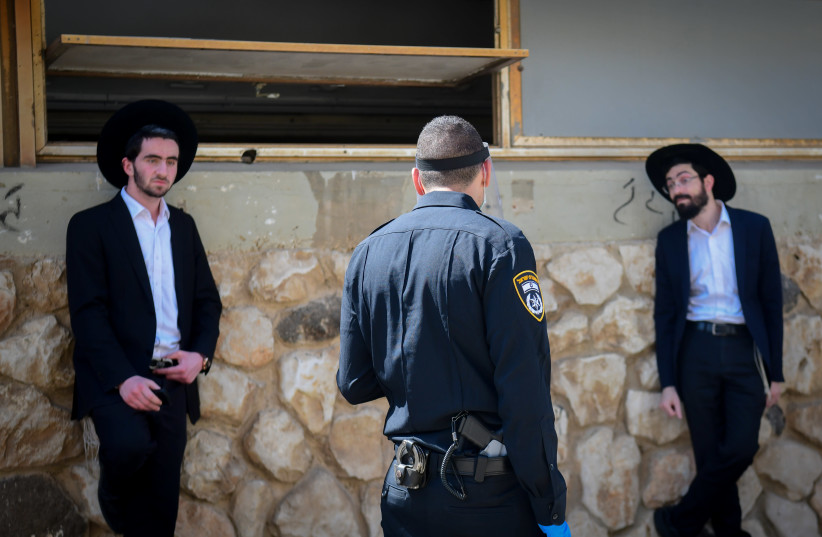 Israeli police officers take out ultra-Orthodox Jewish men from the Ponevezh Yeshiva in Bnei Brak, as part of an effort to enforce lockdown in order to prevent the spread of the coronavirus, April 2, 2020. (photo credit: FLASH90)
