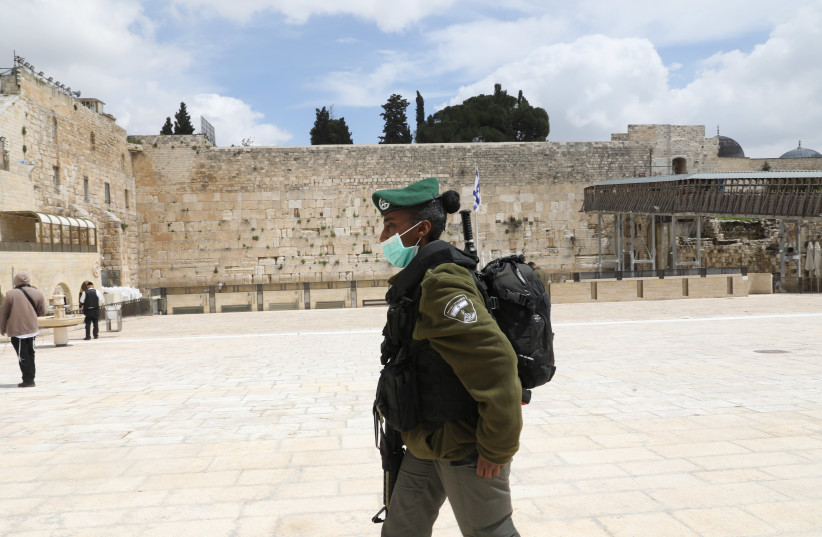 A lone soldier walks past the Western Wall amid the coronavirus pandemic. (photo credit: MARC ISRAEL SELLEM)