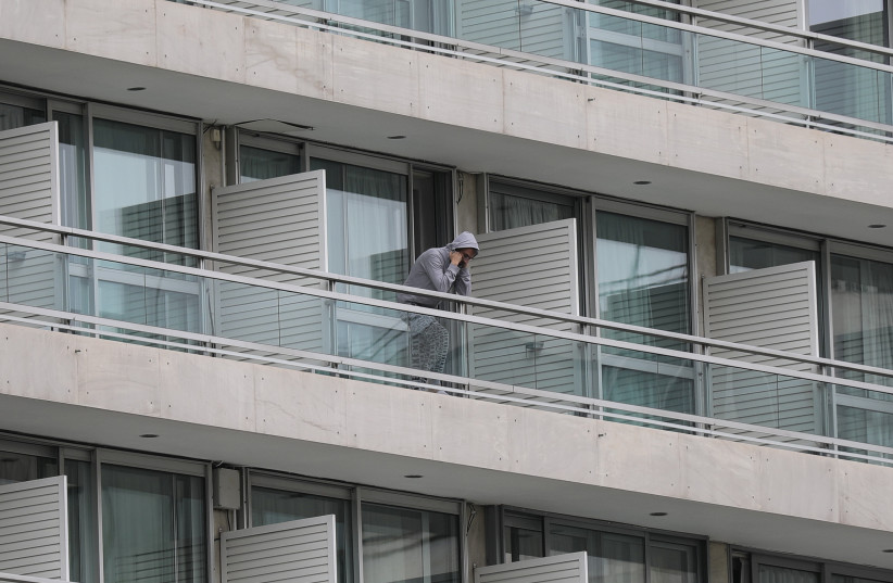 A man, who flew back from Spain, is seen on the balcony of a hotel where he and other passengers were placed in a two-week quarantine, after the Greek government imposed a nationwide lockdown to contain the spread of the coronavirus disease (COVID-19), in Athens, Greece, March 23, 2020 (photo credit: REUTERS/COSTAS BALTAS)