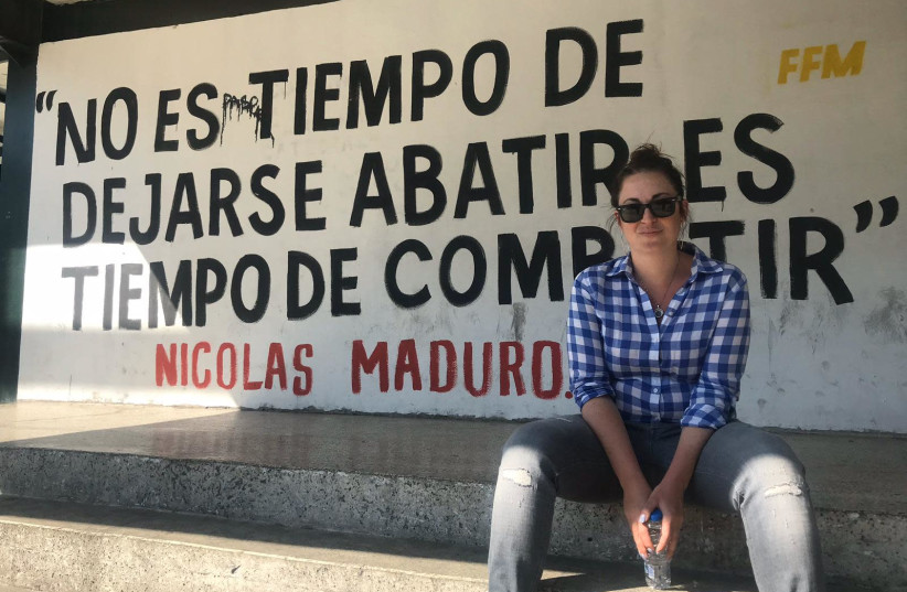 Annika Henroth-Rothstein sits next to a sign with a quote by President Nicolas Maduro in the Venezuelan capital, Caracas. (Annika Henroth-Rothstein) (photo credit: Courtesy)