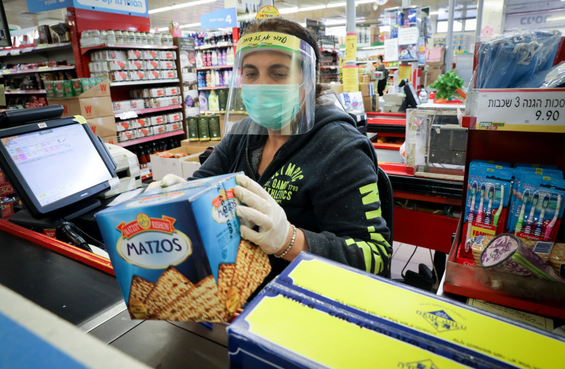 People wear face masks to protect them from the coronavirus as they buy matzot, unleavened bread traditionally eaten during the Jewish holiday of Passover, at a supermarket in Jerusalem. March 31, 2020. (photo credit: YOSSI ZAMIR/FLASH90)