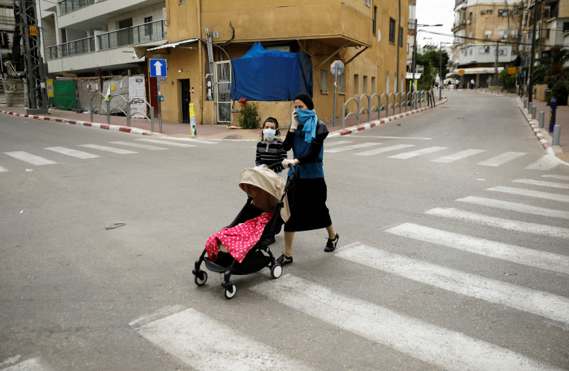 """An ultra-Orthodox Jewish woman crosses a street with her children in Bnei Brak, a town badly affected by the coronavirus disease (COVID-19), and which Israel declared a """"restricted zone"""" due to its high rate of infections, near Tel Aviv, Israel April 5, 2020 (photo credit: REUTERS/AMIR COHEN)"""