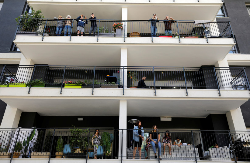 Residents stand on their balcony as they watch Israeli soldiers performing for them in a bid to assist civilians observing government stay-at-home orders to help fight the spread of the coronavirus disease (COVID-19) in Tel Aviv, Israel April 7, 2020. (photo credit: AMIR COHEN/REUTERS)