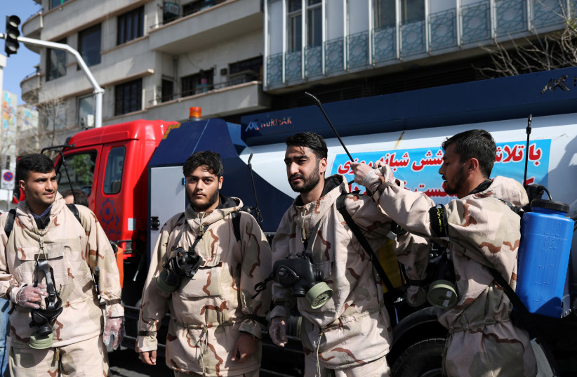 VOLUNTEERS FROM the Basij forces get ready to disinfect the streets, amid coronavirus fears, in Tehran, last week. (photo credit: ALI KHARA/REUTERS)