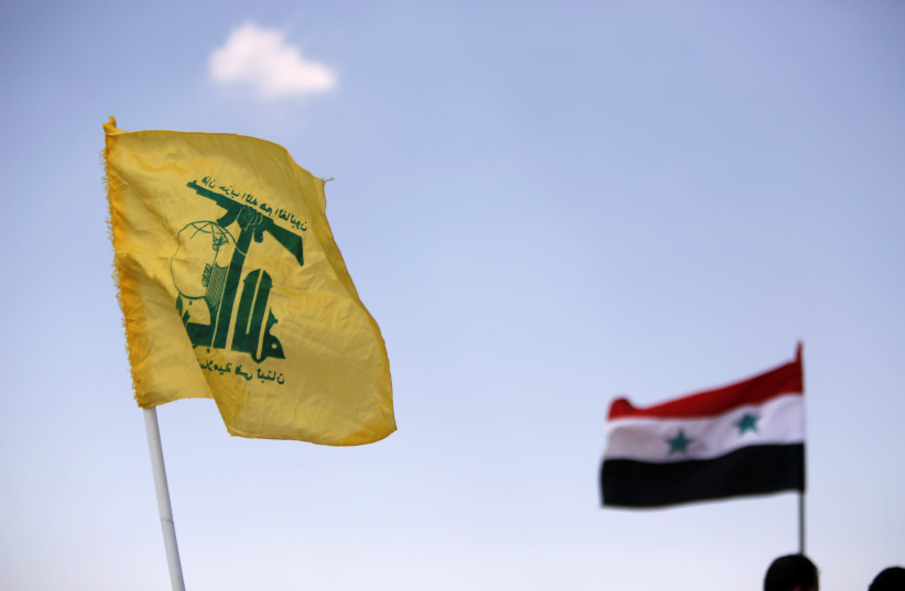 Hezbollah and Syrian flags are seen fluttering in Fleita, Syria, 2017 (photo credit: OMAR SANADIKI/REUTERS)