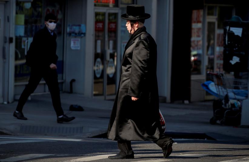 Members of the Hasidic Jewish community walk through the Borough Park neighborhood, during the outbreak of the coronavirus disease (COVID19) in the Brooklyn borough of New York, U.S., April 8, 2020 (photo credit: REUTERS/BRENDAN MCDERMID)