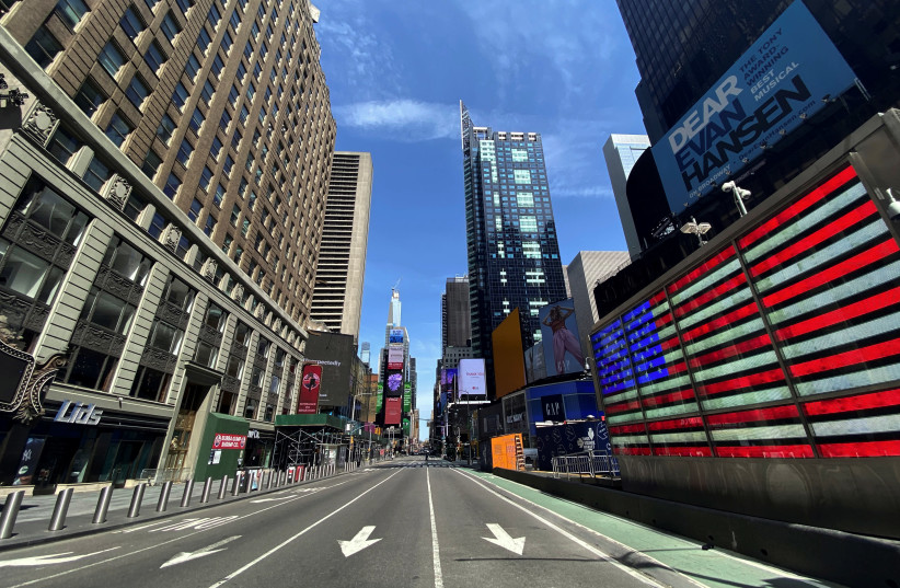 A nearly deserted 7th Avenue in Times Square is seen near midday in Manhattan during the outbreak of the coronavirus disease (COVID-19) in New York City, New York, U.S., April 7, 2020 (photo credit: REUTERS/MIKE SEGAR)