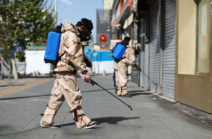 Volunteers from Basij forces wearing protective suits and face masks spray disinfectant in the streets, amid the coronavirus disease (COVID-19) fears, in Tehran, Iran April 3, 2020 (photo credit: WANA (WEST ASIA NEWS AGENCY)/ALI KHARA VIA REUTERS)
