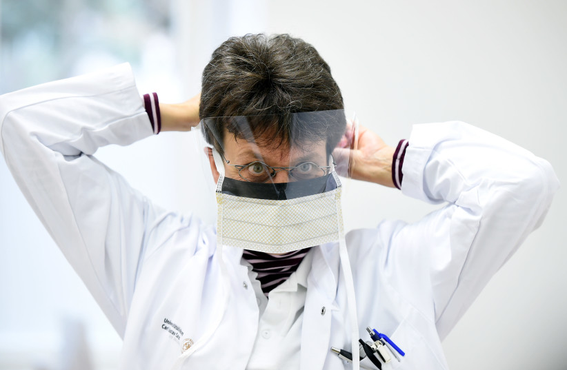 Chief doctor Katja de With puts on a protective mask during a media event in the newly opened coronavirus disease (COVID-19) clearing-up centre in Dresden (photo credit: REUTERS)