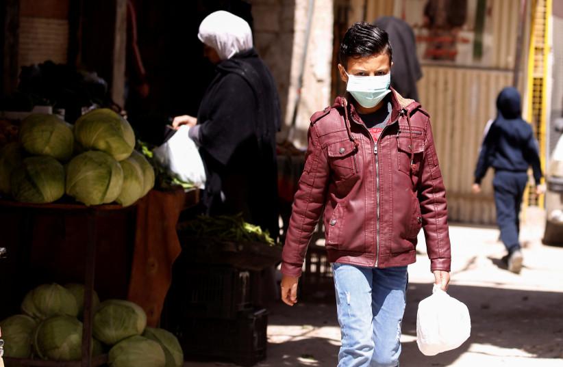 A boy wearing a face mask walks inside Jaramana Palestinian refugee camp, following the outbreak of coronavirus disease (COVID-19), in Damascus, Syria April 1, 2020 (photo credit: REUTERS/OMAR SANADIKI)