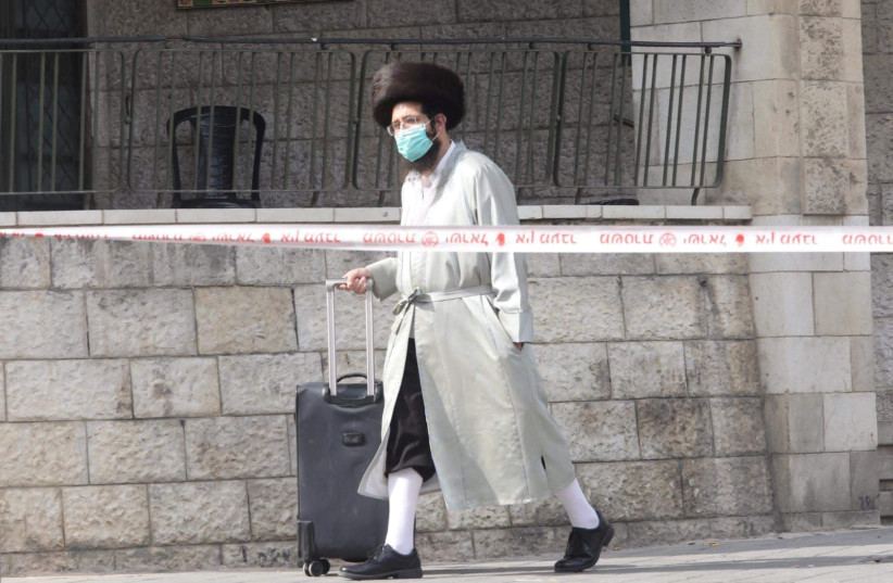 A Haredi man walking with a mask in the neighborhood of Meaa Shearim   (photo credit: MARC ISRAEL SELLEM)