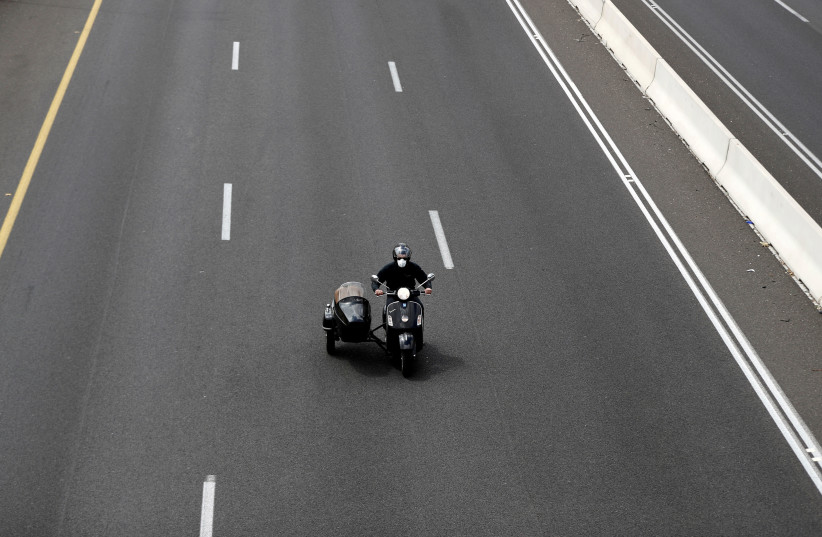 A man wearing a mask drives a motorbike near a roadblock set-up by police as they begin to enforce a national lockdown to fight the spread of the coronavirus disease (COVID-19) on a road leading to Jerusalem, near Ein Hemed, Israel April 7, 2020. (photo credit: REUTERS/Ronen Zvulun)