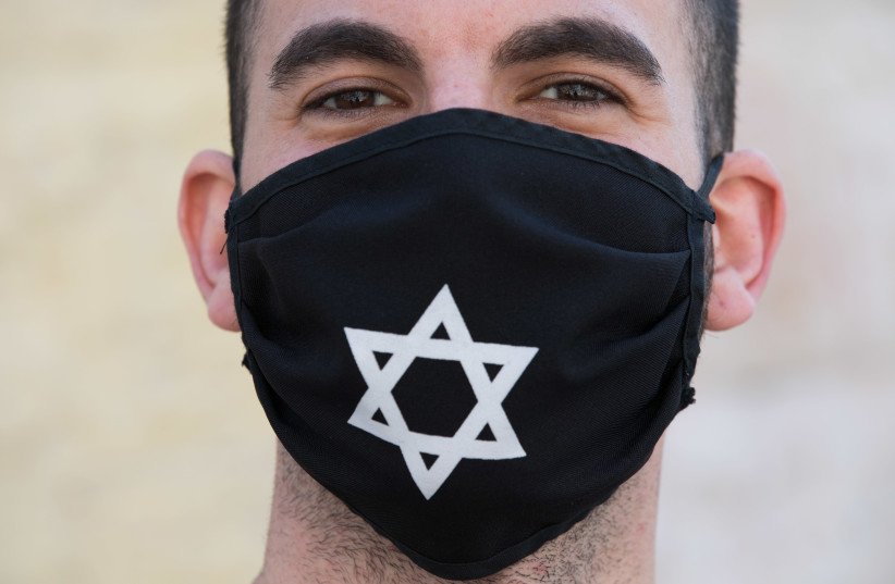 A man wears a face mask  with David Star at the Nachlaot Neighborhood in Jerusalem on April 12, 2020. A full closure on 17 Jerusalem Neighborhoods went into effect today at noon in efforts to contain the spread of the coronavirus. (photo credit: NATI SHOCHAT/FLASH 90)