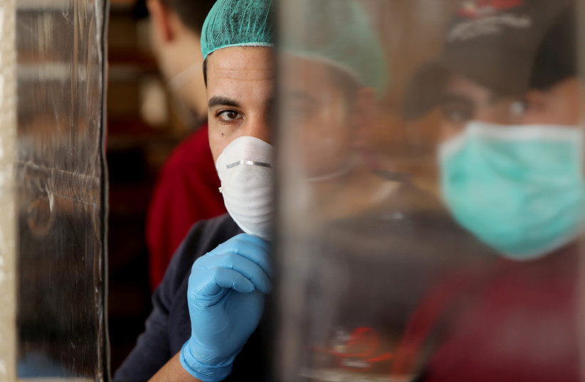 Palestinians, wearing masks as a preventive measure against the coronavirus disease, work in a bakery in Gaza City (photo credit: REUTERS/MOHAMMED SALEM)