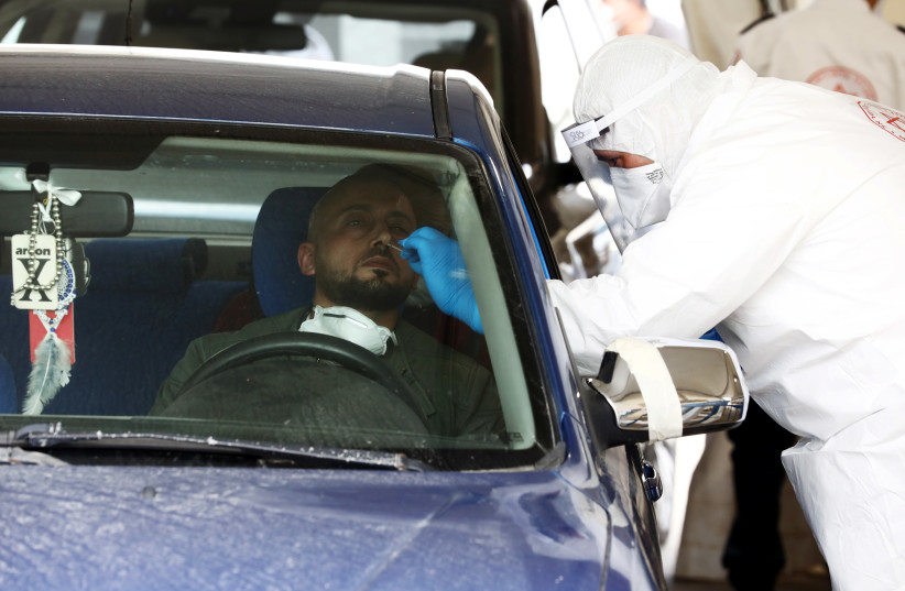 A nose-swab is taken from a driver at a drive-through coronavirus testing station in east Jerusalem, amid coronavirus disease (COVID-19) outbreak April 2, 2020. (photo credit: AMMAR AWAD / REUTERS)