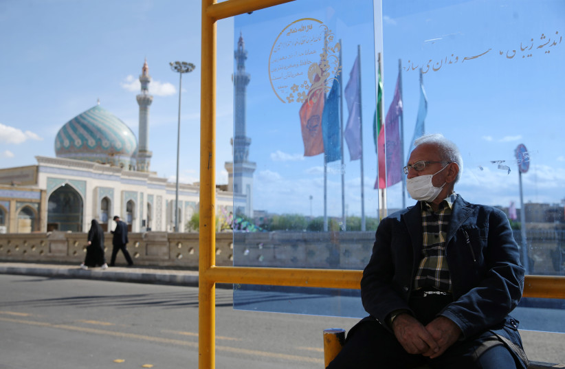 A man wearing a protective face mask, following the outbreak of coronavirus disease (COVID-19), sits at a bus stop in Qom, Iran March 24, 2020 (photo credit: REUTERS)