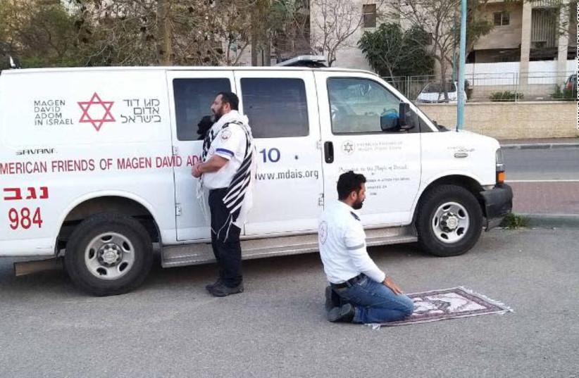A Jewish Magen David Adom volunteer stands next to a Muslim MDA volunteer. (photo credit: MOHAMD ALNBARE/MDA SPOKESPERSON)