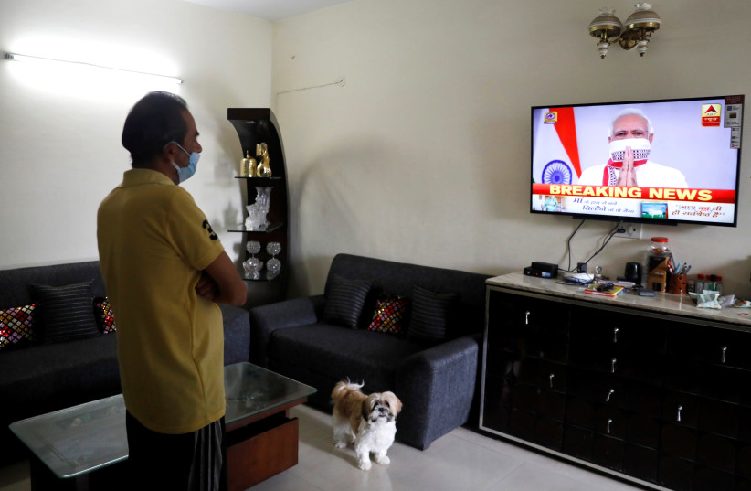 A man watches India's Prime Minister Narendra Modi's address to the nation on a television announcing the extension of a nationwide lockdown till May 3, to limit the spreading of coronavirus disease (COVID-19), in in New Delhi, India, April 14, 2020. (photo credit: REUTERS/ANUSHREE FADNAVIS)