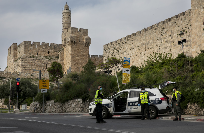 """Police at a temporary """"checkpoint""""  outside the david tower in the Old City of Jerusalem on April 15, 2020, to check if people are not disobeying the governments orders on a lockdown, in order to prevent the spread of the Coronavirus. (photo credit: OLIVIER FITOUSSI/FLASH90)"""