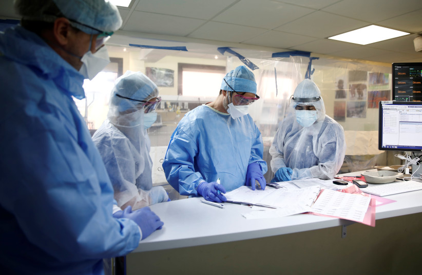 Medical staff, wearing protective suits and face masks, work in an intensive care unit for coronavirus disease (COVID-19) patients at the Franco-Britannique hospital in Levallois-Perret near Paris as the spread of the coronavirus disease continues in France, April 15, 2020. (photo credit: REUTERS)