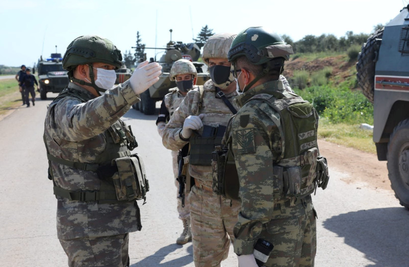 Turkish and Russian soldiers wearing face masks are pictured during a joint patrol in the northern Idlib province in Syria, Wednesday.  (photo credit: REUTERS)