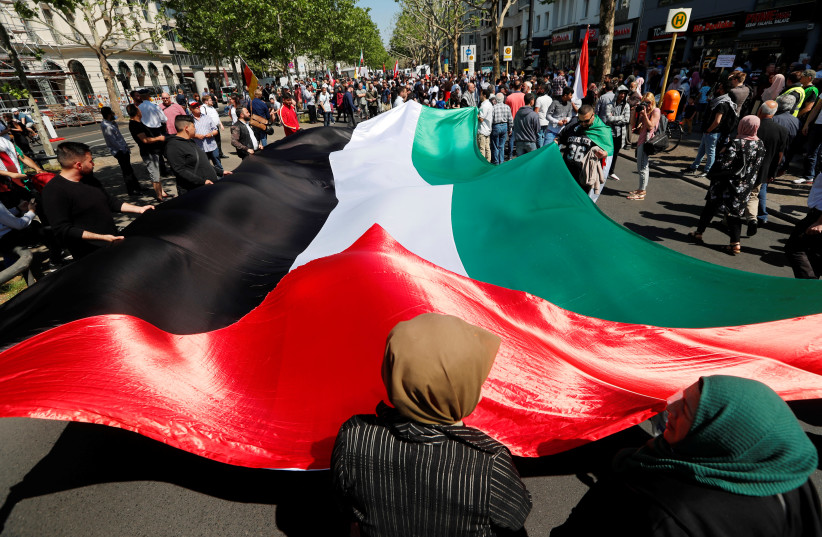 Protesters hold a large Palestinian flag during a demonstration marking al-Quds Day (Jerusalem Day), in Berlin, Germany June 1, 2019 (photo credit: REUTERS/FABRIZIO BENSCH)