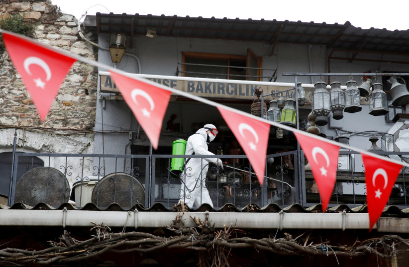 FILE PHOTO: A worker in a protective suit sprays disinfectant at Grand Bazaar, known as the Covered Bazaar, to prevent the spread of coronavirus disease (COVID-19), in Istanbul, Turkey, March 25, 2020 (photo credit: REUTERS/UMIT BEKTAS/FILE PHOTO)