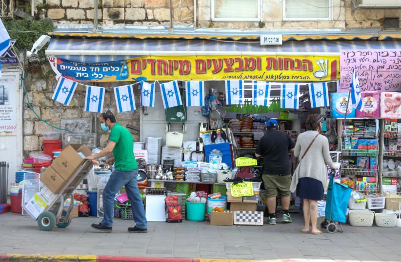 A shop opens at Agripas street in Jerusalem next to the Machane Yehuda market (photo credit: MARC ISRAEL SELLEM/THE JERUSALEM POST)