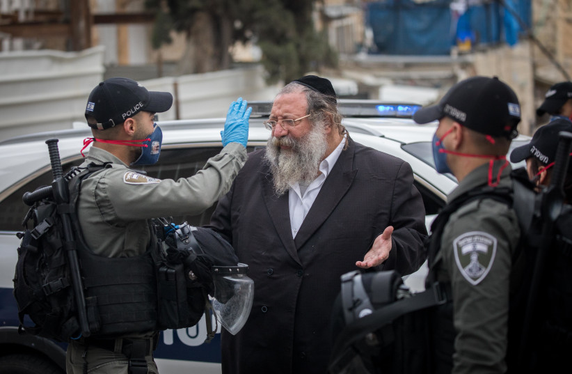 Police officers close synagogues and handing out fines to ultra orthodox Jews at the Bukharim quarter in Jerusalem, following the government's decisions, in an effort to contain the spread of the coronavirus, April 17, 2020 (photo credit: YONATAN SINDEL/FLASH 90)