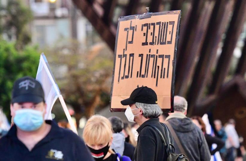 A man in the Black Flag protest on Sunday April 19 2020 in Tel Aviv, the sign says 'When [Prime Minister Benjamin Netanyahu] Bibi will go, the coronavirus will go  (photo credit: AVRAHAM SASSONI)
