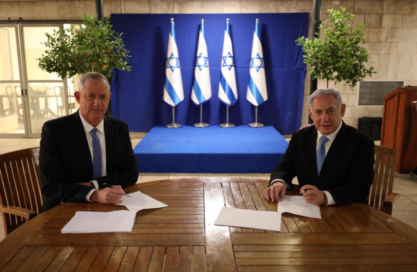 Prime Minister Benjamin Netanyahu and Blue and White leader Benny Gantz sign a unity government agreement (photo credit: Courtesy)
