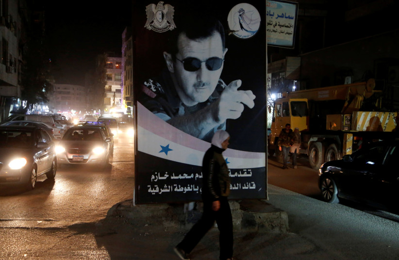 A woman walks past a poster depicting Syria's President Bashar al-Assad in Damascus, Syria March 5, 2020 (photo credit: REUTERS/YAMAM AL SHAAR)